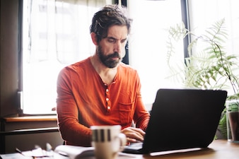 Serious man using laptop at workplace