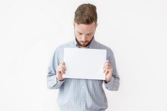 Серьезный человек с пустым листом бумаги