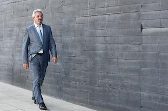 現代的なオフィスビルの外を歩く真剣な高齢者のビジネスマン。