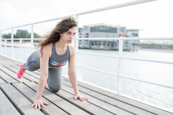 Serious Sporty Girl Exercising on City Quay