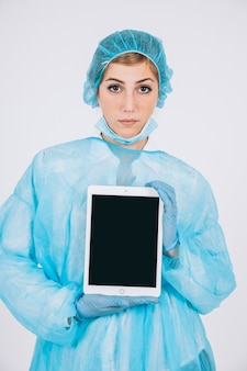 Serious surgeon holding tablet