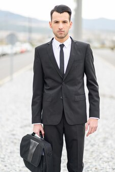 Serious worker holding his briefcase