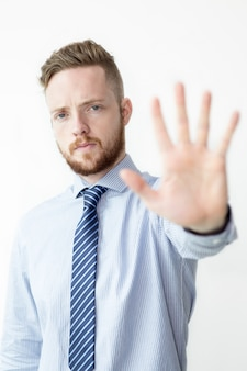 Serious Young Business Man Showing Palm