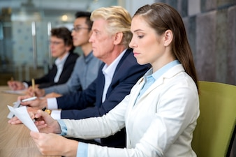 Serious young businesswoman sitting at conference