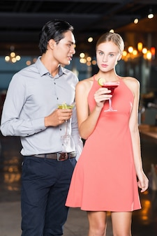 Serious Young Couple with Cocktails at Party