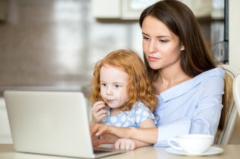 Serious young mother using laptop with daughter