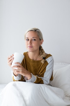 Serious young woman sitting on bed holding cup