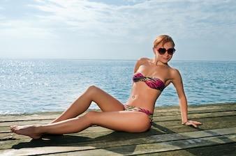 桟橋でビキニを着てセクシーな赤い女の子