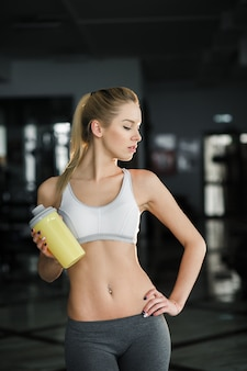 Sexy woman with yellow bottle at the gym