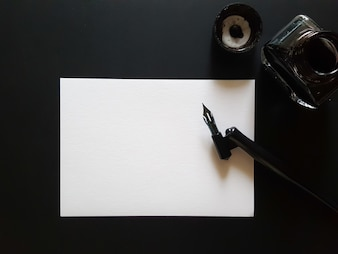 Sheet of paper, pen and ink of black on black office desk.
