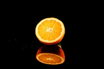 オレンジの光沢のある半分は、黒の背景に黒いガラスのテーブルの上に立つ