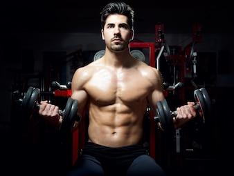 Shirtless strong man lifting dumbbells