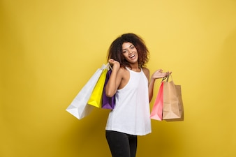 Shopping Concept - Close up Portrait young beautiful attractive African woman smiling and joyful with colorful shopping bag. Yellow Pastel wall Background. Copy Space.