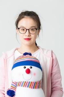 クリスマスの雪だるまを保持している若いアジアの女性のスタジオで撮影