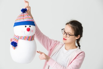 Shot in the studio of the young asian woman holding a Christmas Snowman
