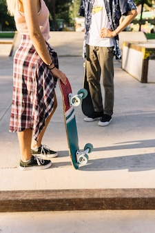 Side view of young skater couple