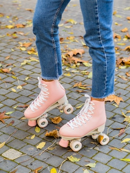 Side view of woman wearing jeans with roller skates