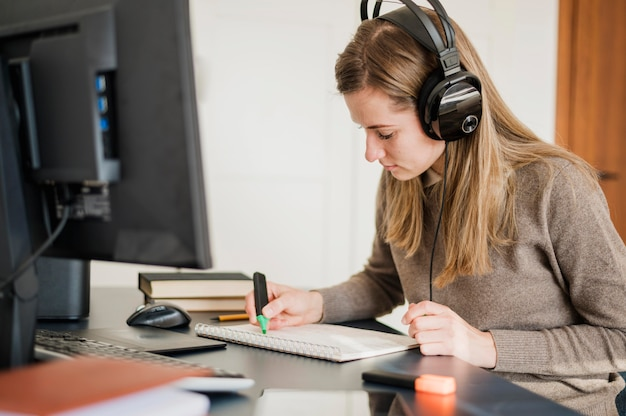 Side view of woman with headphones at desk participating in online class