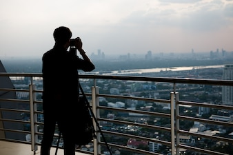 Silhouette man taking photo of city
