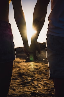 Silhouette of couple holding hands at the beach