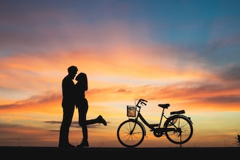 Silhouette of couple in love kissing in sunset. Couple in love concept.