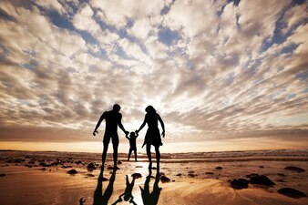 Silhouette of family playing on the beach