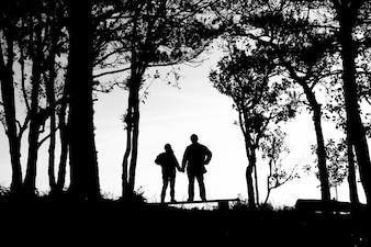 Silhouette of love couple in trees border, back and white tone