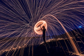 Silhouette of man making a circle of sparks at night