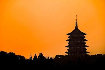 Silhouette of oriental building with orange sky