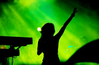Silhouette of woman singing on green background