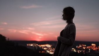 Silhouette of woman with a city background