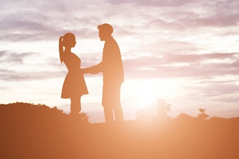 Silhouette of Young couple holding hands with mountain sunset ba