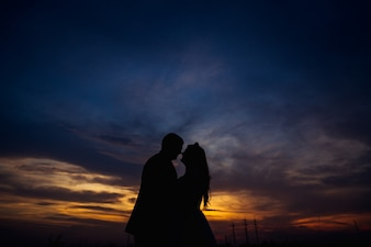 Silhouettes of tall man and long-haired woman kissing under mysterious sky