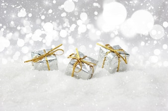 Silver christmas gifts nestled in snow