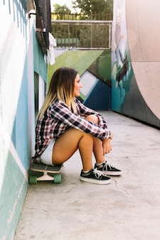 Skater girl sitting on board