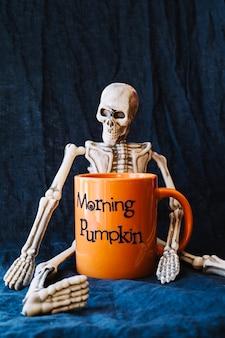 Skeleton with orange mug