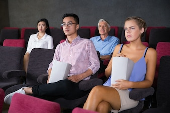 Skeptical Caucasian woman watching movie in cinema