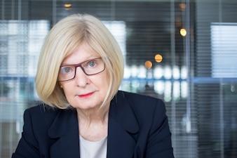 Skeptical senior businesswoman looking at camera