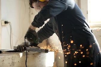 多くのスパークを伴う金属プロファイルのパイプを研削する熟練労働者