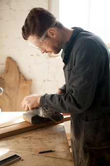 Skilled young carpenter doing woodwork, working with electric sander, vertical