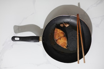 Skillet with cooked fish and chopsticks