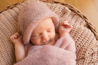 Sleeping baby with hands raised