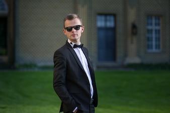 Slim man in sunglasses standing