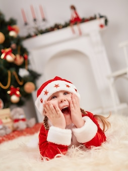Small child dressed as santa claus with hands on face