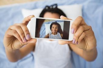 Smartphone in hands of happy woman taking selfie