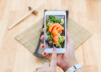 Smartphone taking Sashimi salmon