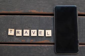 白い画面と旅行のアルファベットのスマートフォン