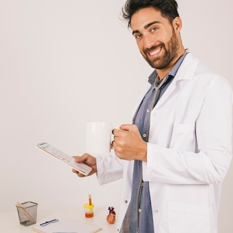 Smiley doctor posing with ipad and coffee