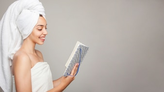 Smiley woman reading after bath and copy space