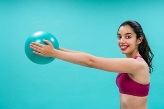 Smiley woman training with a ball